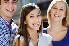 Three young people smiling. Portrait of young people outdoors Royalty Free Stock Photography
