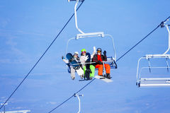 Three young people with snowboarders on ropeway Royalty Free Stock Photography