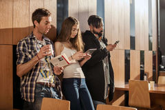 Three young people standing in the room near the wall with gadgets in their hands. Stock Images