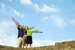 Three young people staying with raised hands. Against blue sky Stock Images