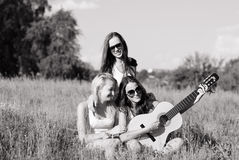 Three young people teenage girls playing guitar. On summer day sitting in high grass black and white image Stock Photography