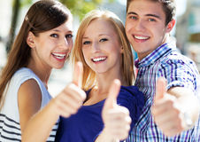 Three young people with thumbs up. Portrait of young people outdoors Stock Image