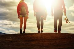 Three young people, two girls and a guy, in the hands of longboards stock image