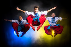 Three young people in the Ukrainian national costumes dance and jump on a dark background with smoke stock photo