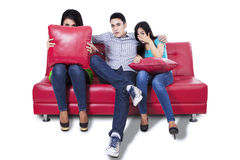 Three young people watching TV Stock Photo