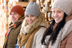 Three young people winter fashion wooden logs. Three young people posing winter fashion leaning against wooden logs Royalty Free Stock Image