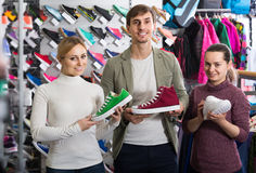 Three young persons showing an assortment of the shoes in the st. Cheerful three young european persons showing an assortment of the shoes in the store stock image
