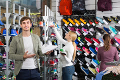 Three young persons showing an assortment of the shoes in the st Royalty Free Stock Image