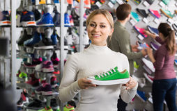 Three young persons showing an assortment of the shoes in the st. Happy three young persons showing an assortment of the shoes in the store royalty free stock photos