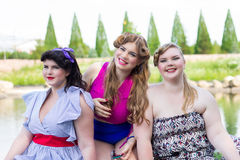 Three young plus size model sitting by the lake Royalty Free Stock Image