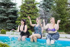 Three young plus size model splashing in the pool outdoors. Three young beautiful plus size model splashing in the pool outdoors, splash water. Professional Stock Image