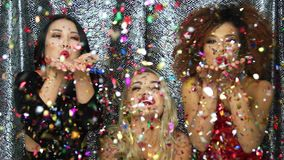 Pretty women blowing on confetti. Three young pretty female models in glamour dresses standing together and blowing on glittering confetti on hands stock video footage
