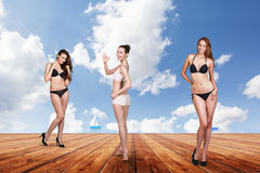Three young pretty women posing on the pier. Royalty Free Stock Images