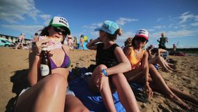 Three young pretty women joyfully sit on sandy beach sunny summer day. Three young pretty women wearing sunglasses, hats and swimming suits joyfully sit on stock video