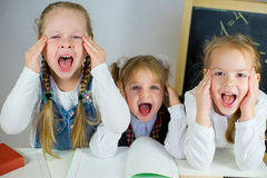 Three young schoolgirls sitting at the table Stock Photo