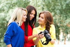 Three young sexy female photographers watching photos Stock Photography