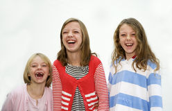 Three young sisters laughing. Three young girls, sisters standing laughing together Royalty Free Stock Photo