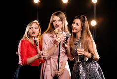 Three young smiley beautiful women in karaoke Stock Photos