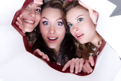 Three Young Smiling Women. Looking into the paper shopping bag stock photo