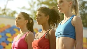 Three young sportswomen standing in one line, attentively listening to coach. Stock photo royalty free stock photos