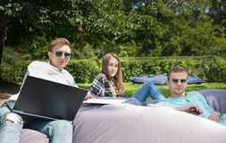 Three young student friends relaxing outdoors on a big cushion,. Three young student friends relaxing outdoors in the park on a big cushion, they are looking at stock image