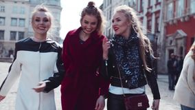 Three young stylish women walking, talking, laughing in the city-center. Fashionable look, amazing red coat. True stock video footage