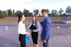 Three young successful businessman, students communicate, smilin Royalty Free Stock Images