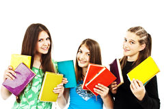 Three young teenage girls with colored books Stock Images
