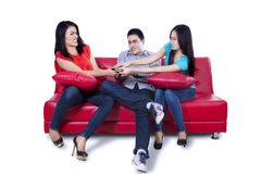 Three young teenagers fighting for remote control Stock Photos