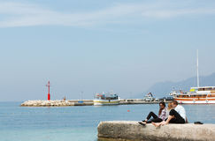 Three young teenagers sitting on the shore of the Adriatic Sea and talk. Stock Images