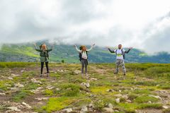 three young tourists with backpackers standing in a row on a hill in the background of a mountain and amusingly holding the cloud stock images