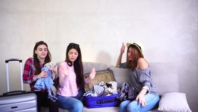 Three young travellers on trip and preparing suitcases on couch in afternoon room. Funny travel friends together collect large gray and blue suitcases, add up stock video