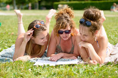 Three young woman on the beach reading a magazine Stock Photography