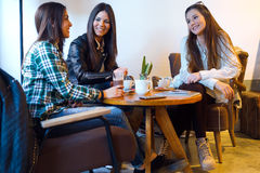 Three young woman drinking coffee and speaking at cafe shop. Stock Photos