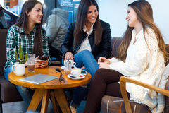 Three young woman drinking coffee and speaking at cafe shop. Stock Images