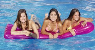 Three young woman floating on an air mattress stock video footage