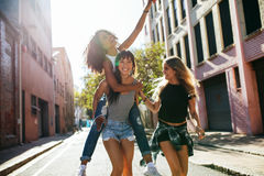 Three young woman having fun on city street. Outdoor shot of young women carrying her female friend on her back. Three young women having fun on city street royalty free stock photo