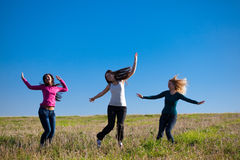 Three young  woman jumping into the field Stock Photography