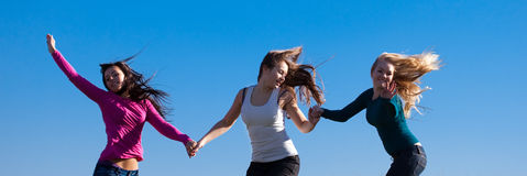 Three young  woman jumping into the field Royalty Free Stock Image
