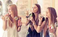 Three young woman making soap bubbles Stock Photo