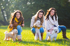 Three young woman with their pet dogs Royalty Free Stock Image