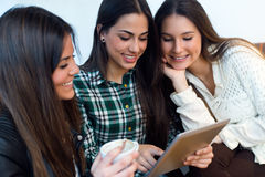 Three young woman using digital tablet at cafe shop. Royalty Free Stock Photo