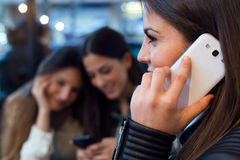 Three young woman using mobile phone at cafe shop. Royalty Free Stock Photo