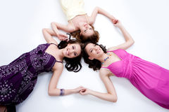 Three Young Women. Lying on a white background and holding each other hands stock photography