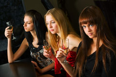 Three young women in a bar. Stock Photos