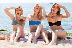 Three young women in bikini on sandy beach Stock Image