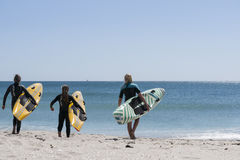 Three young women carry their surfboards. Stock Photo