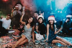 Three Young Women Celebrating New Year on Party. Santa Claus Cap. People in Red Caps. Happy New Year Concept. Glass of Champagne. Celebrating of New Year royalty free stock photo