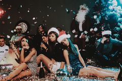 Three Young Women Celebrating New Year on Party. Santa Claus Cap. People in Red Caps. Happy New Year Concept. Glass of Champagne. Celebrating of New Year stock photo