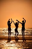 Three Young Women Dancing On Beach At Sunset Stock Photos